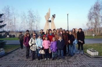 Учасники екскурсії на фоні скульптури «Символ миру», спорудженої на території заповідника в 2012 р.