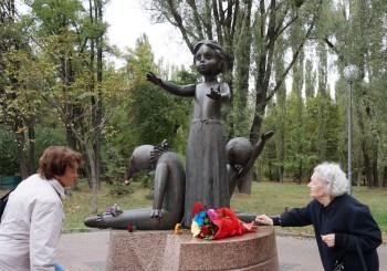 Колишні малолітні в'язні фашизму Зоя Іванівна Кривич (праворуч) і Зінаїда Євдокимівна Синицька (ліворуч) покладають квіти до пам'ятника дітям, розстріляним у Бабиному Яру